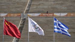 A member of security walks in the stadium behind the Chinese, Olympic and Greek flag prior to the Olympic flame handover ceremony at Panathinean stadium in Athens, Greece, Tuesday, Oct. 19, 2021. The flame will be transported by torch relay to Beijing, China, which will host the Feb. 4-20, 2022 Winter Olympics.