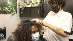 Many Flores, co-owner of The Texture Temple, cut Nickie Martinez's hair on a recent Friday afternoon.
