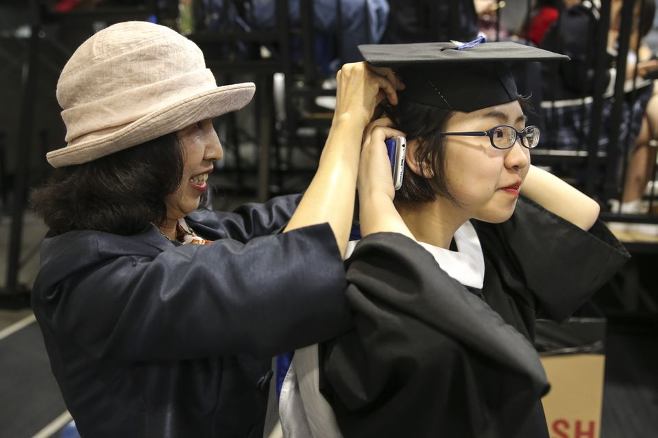 Shumei Ma helped her daughter, Meng Diao, adjust her hair and cap before the ceremony.