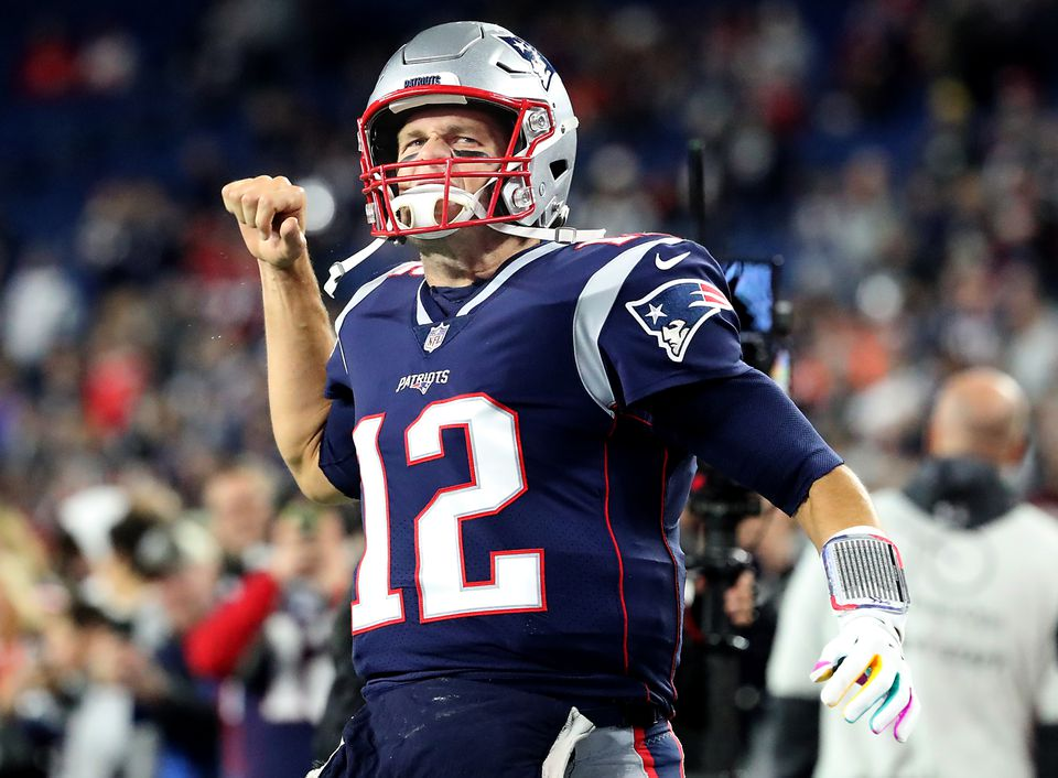 Tom Brady pumps his fist after running onto the field.