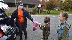 Samantha Ruiz-Bueno, left, passes out candy to Boaz Pettis, 6, of Millcreek Township, Pa., and his sister Callista Pettis, 8, during the Drive-thru Trunk or Treat event for kids at the Fairview United Methodist Church, Saturday, Oct. 31, 2020, in Fairview, Pa.
