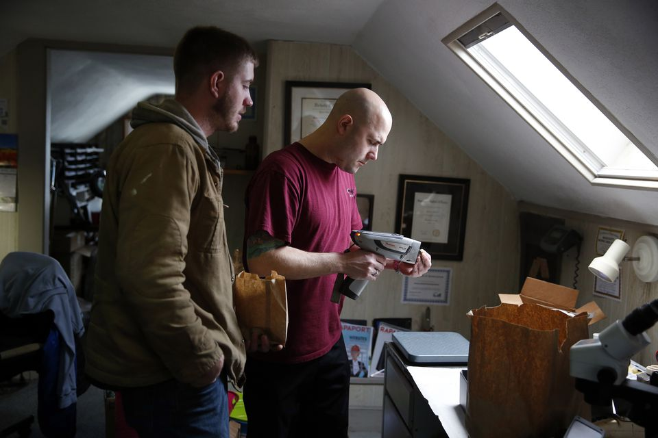 Jason Nyborn (right) of Precious Metals Reclaiming Service in Westwood tested the content of a computer part that was brought in by Wesley Bucklin of MW Recycling in Biddeford, Maine.