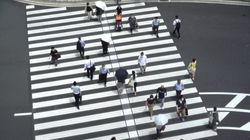 People walked near Tokyo Station in Tokyo Thursday, a day after the record-high coronavirus cases were found in the Olympics host city.