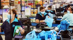 Cashier Diana Rivero stands behind a partial protective plastic screen and wears a mask and gloves at the Presidente Supermarket in Miami in April, 2020.