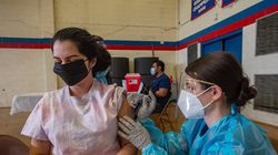 Angelica Romero, 30, is inoculated with the Moderna Vaccine for Covid-19 by pharmacy student Kayla Sepe at Central Falls High School in Central Falls, Rhode Island.