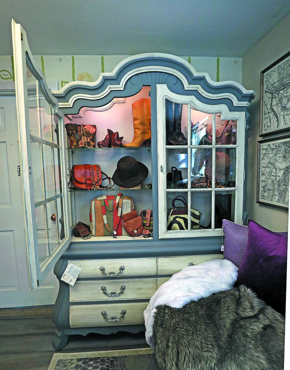A cabinet was repurposed as a closet for bags, footwear, and the like.