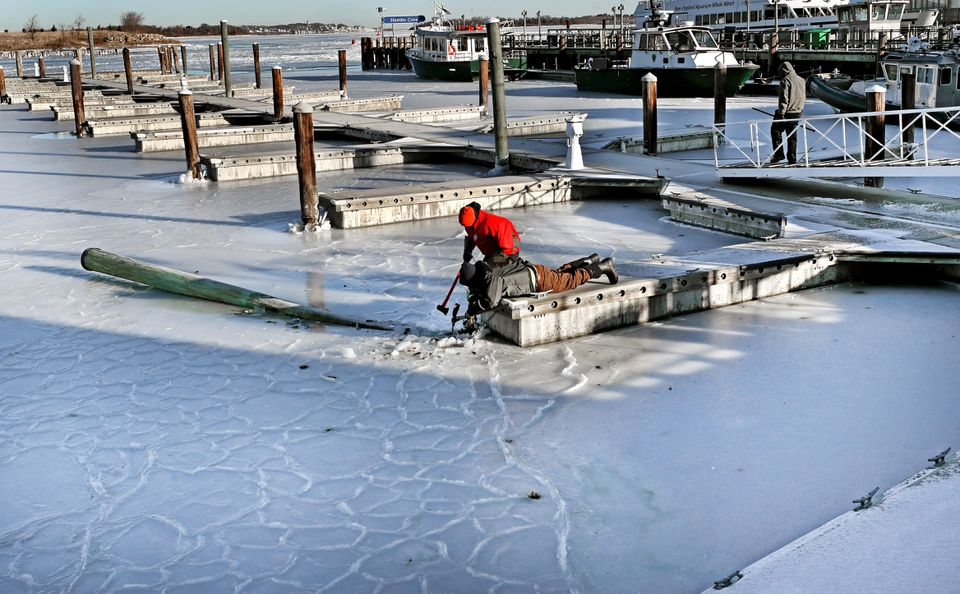 Tyler Borris (right) and Willie Fessenden with Hingham Shipyard Marinas free up a finger dock and a piling that snapped off from the ice. (David L Ryan/Globe Staff)