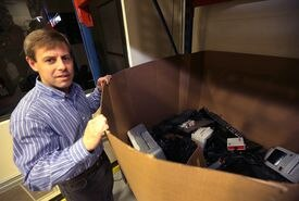 Dodd Corby, CEO at SmartPak in Plymouth, looks over a box of electronic items, including personal items brought in by employees,  that were collected to be recycled.