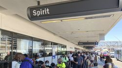Passengers line up outside the Spirit Airlines terminal at Los Angeles International Airport in Los Angeles on Tuesday, Aug. 3, 2021. Spirit Airlines canceled more than half its schedule Tuesday, and American Airlines struggled to recover from weekend storms at its Texas home, stranding thousands of passengers at the height of the summer travel season.