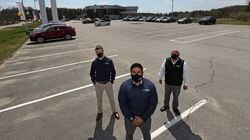 Robert George, sales representative, Shahid Qureshi, sales manager, and Walter Aguilar, sales and leasing professional, at Prime Toyota-Route 2 in Lancaster. The lot is usually full of cars, but a shortage of microprocessor chips has delayed vehicle deliveries.