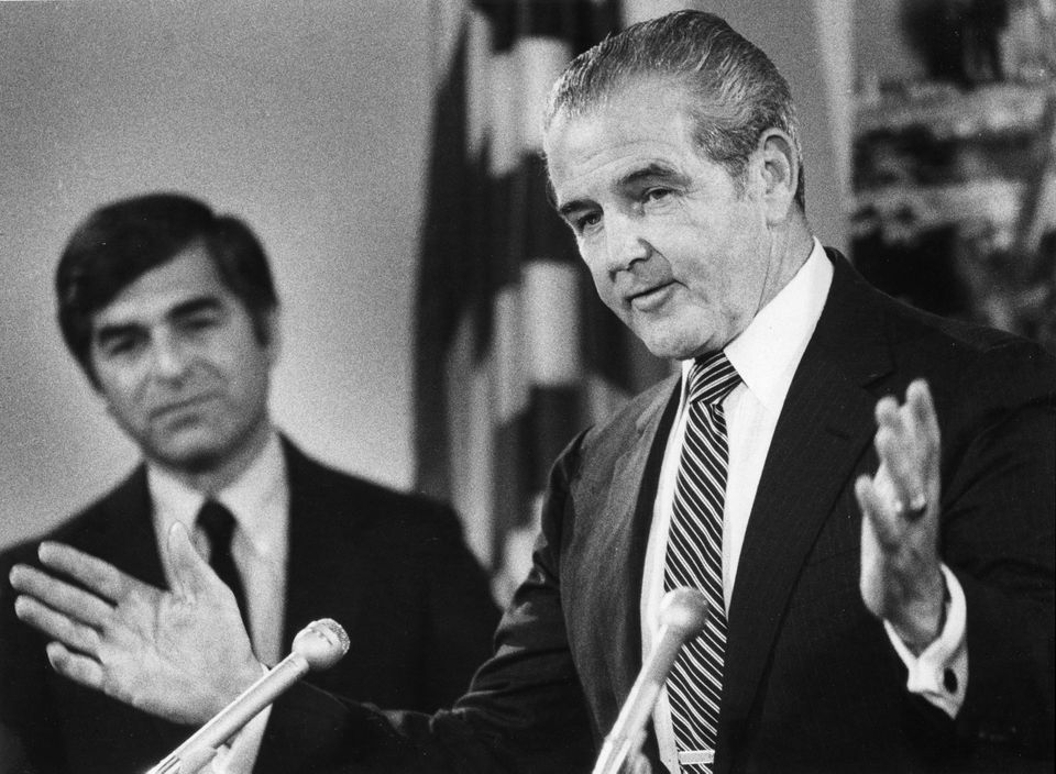 John Driscoll (right), chairman of the Massachusetts Turnpike Authority, spoke during a press conference at the office of Governor Michael Dukakis (left) in June 1983.