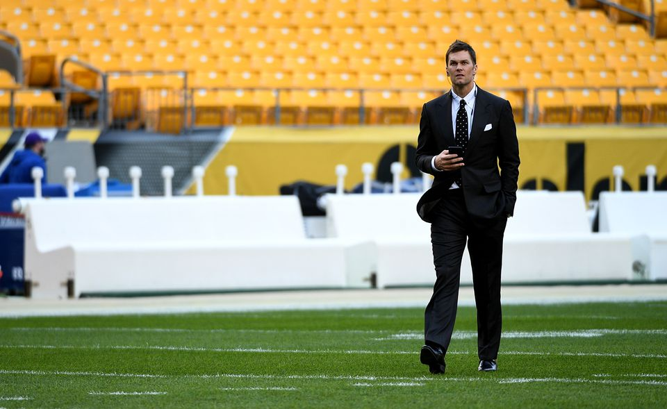 Tom Brady walks off the field after surveying it before the game.