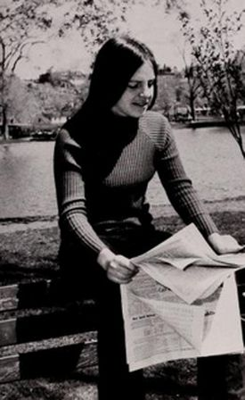 In a University of Massachusetts Boston yearbook photo, Eileen Myles sits at Boston Common looking through the classifieds.