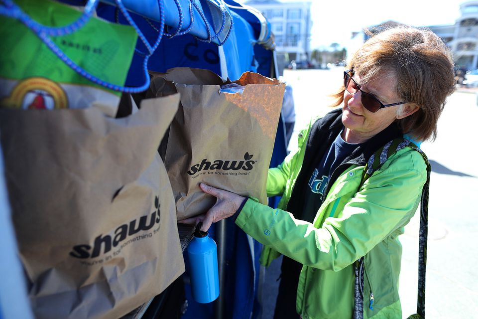 Cindy Whitlock from Washington State loaded grocery bags from Shaws in Hyannis into luggage carts at the Hyannis Ferry Terminal parking lot. She shopped for her daughter, Jo, who lives on Nantucket.
