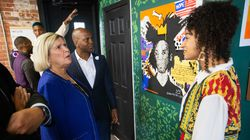 Barbara Papitto of the Papitto Opportunity Connection foundation, left, and board advisor Arnell Milhouse, center, chat with artist Lexus Fernandez of Providence about her painting inside the new   Haircuts and Heritage barber shop in Pawtucket, R.I., on Sept. 17, 2021.
