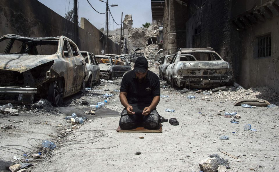 An Iraqi Counter-Terrorism Services member prays in the Old City of Mosul on July during an ongoing offensive to retake the city from Islamic State group fighters.