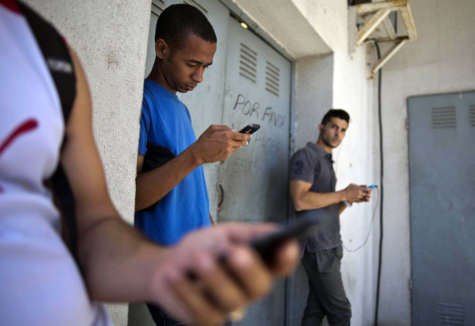 Students gathered behind a business looking for Internet signal for their smart phones in Havana, Cuba.