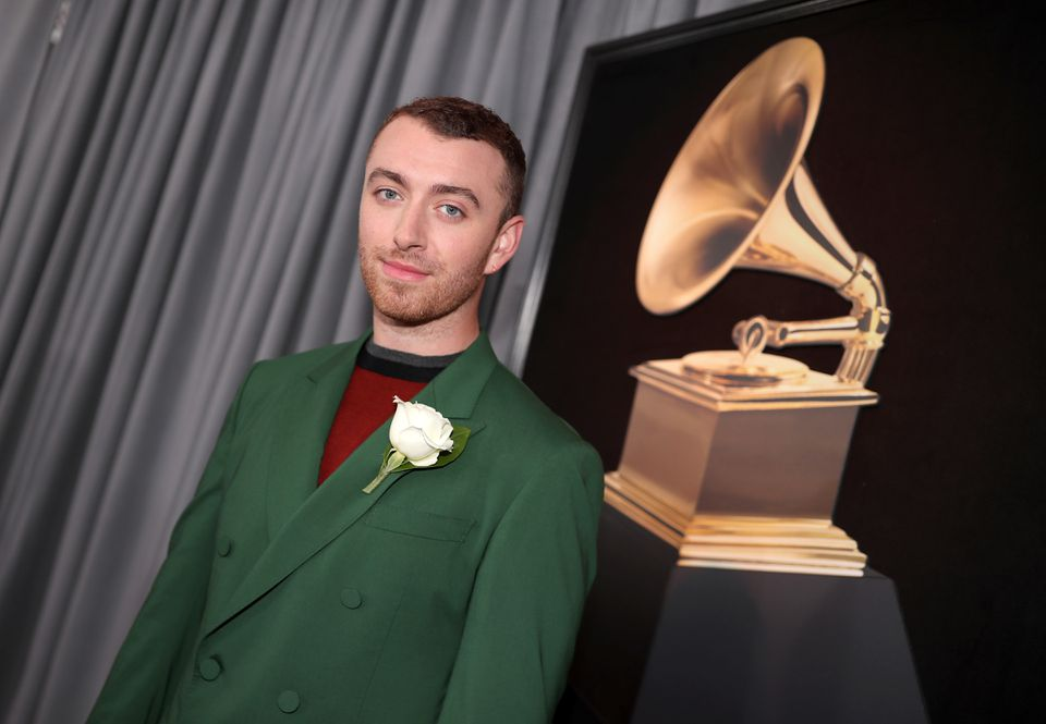 Sam Smith was in a green suit, white rose in place and a red scoop-neck shirt underneath.