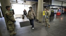 In this file photo, members of the Rhode Island National Guard, left, and right, greet disembarking train passengers on March 30, 2020, at Providence Station to provide them with information about the coronavirus and advise them to self-quarantine for 14 days if they are arriving from out of state.