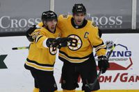 Boston Bruins' Patrice Bergeron, right, celebrates with Brad Marchand, left, after Marchand scored against the Pittsburgh Penguins.