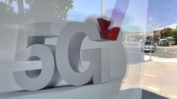 A 5G sign is displayed in a window at a Verizon store in Corte Madera, Calif.