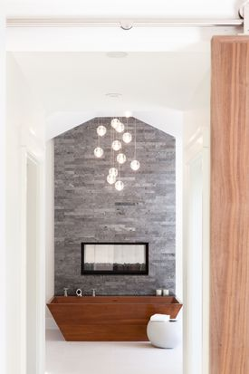 Above the tub, another handcrafted iroko piece, striking cast-glass Bocci pendant lights add dramatic sparkle.