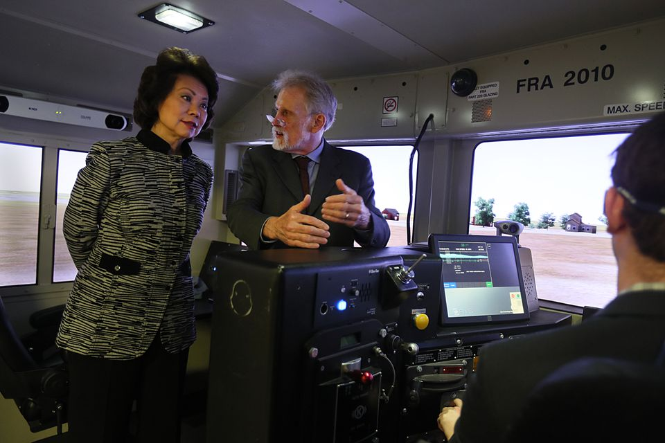Donald Fisher showed a simulator to Transportation Secretary Elaine Chao at the Volpe National Transportation Systems Center last week.