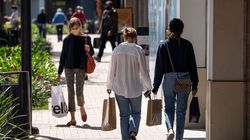 Shoppers wearing protective masks carry bags in the Broadway Plaza Shopping Center in Walnut Creek, California.