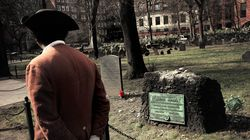 In this March 3, 2020, photo Samuel Ike, of Cambridge, dressed in the role of Revolutionary War-era Black abolitionist Prince Hall, walks past the Granary Burying Ground in Boston. The city was marking the 250th anniversary of the Boston Massacre.