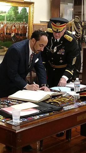 Retired US Air Force Lt. Col. Vincent J. Perrone signs the historic membership book of the Ancient and Honorable Artillery Company of Massachusetts while Captain Commanding Brigadier General Robert E. Welch looks on.