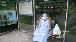 Marie T. Conserle kept dry from the rain while waiting for the bus on Blue Hill Avenue in Mattapan on Sunday.