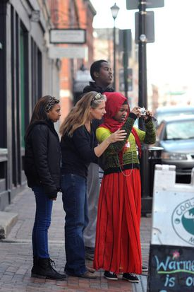 Molly McGrath (second from left) helps Nadifo Nur, 16, shoot a picture for a project, with Lauren Slaughter (left), 16, and Hassan Omar, 15.
