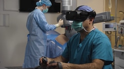 An image provided by Vicarious Surgical showing how a surgeon would use a virtual reality headset to operate the robotics machine in the background.