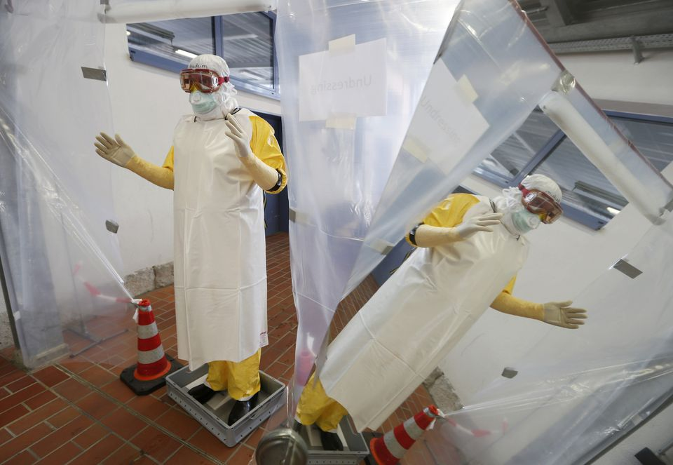 A doctor is decontaminated after taking a blood sample from a mock Ebola patient during a training session held in Germany.