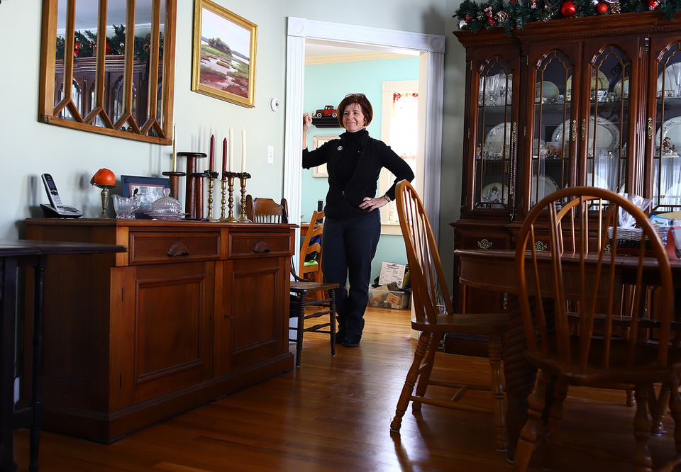 Meg Gaudet stands by a refinished bookcase, inherited from her late mother, that came without a top. The mirror was made from a window.