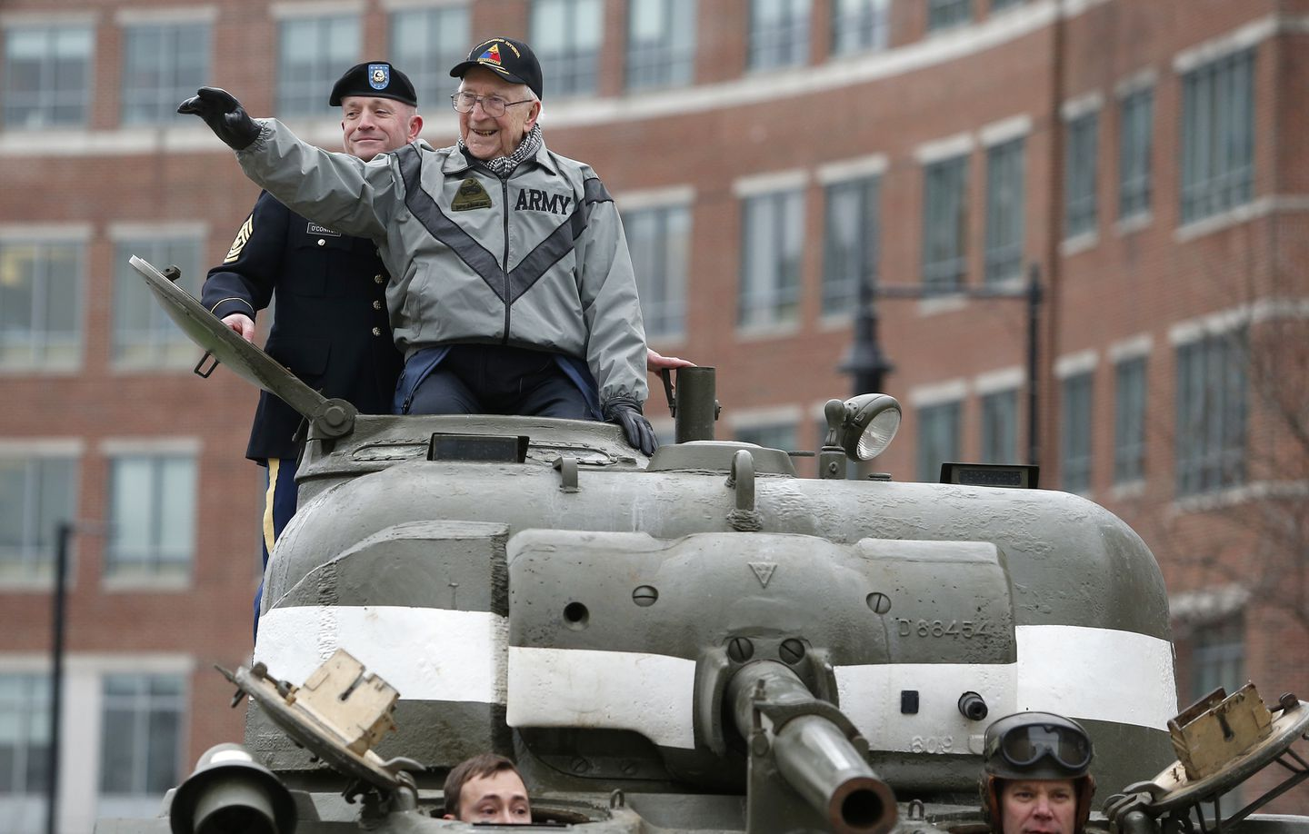 Clarence Smoyer waved as he rode in a Sherman tank to the Charlestown Navy Yard on Wednesday.