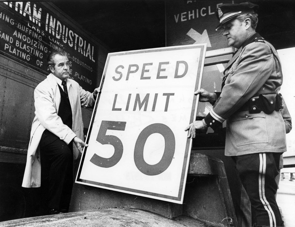 Mr. Driscoll (left) and Captain James Kiloran (right) placed a speed limit sign at the entrance of the turnpike in Allston on Nov. 13, 1973.