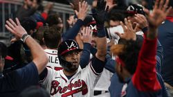 Atlanta Braves' Eddie Rosario, center, celebrates after hitting a three-run home run during the fourth inning in Game 6 of the National League Championship Series against the Los Angeles Dodgers.