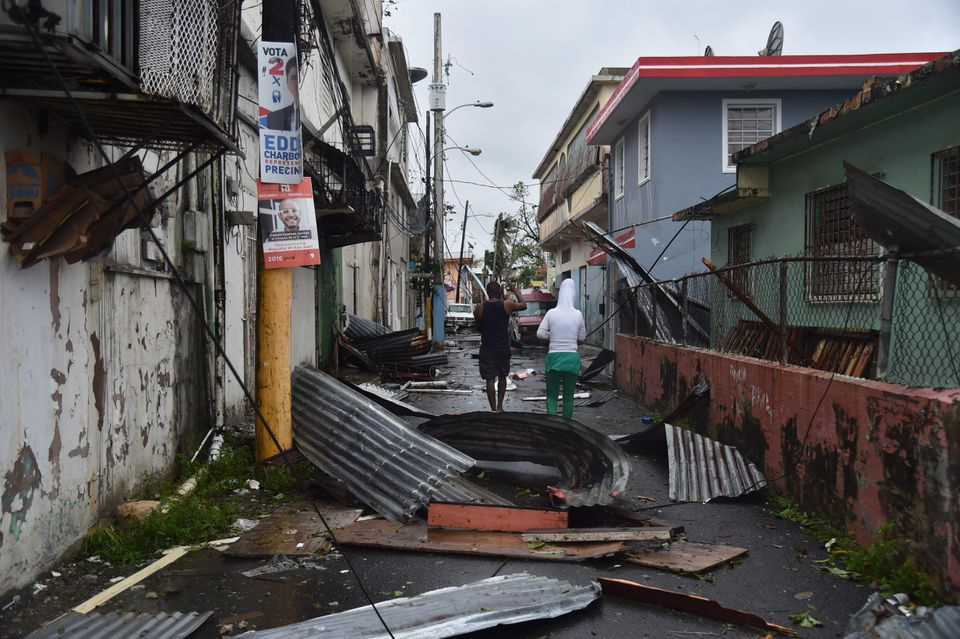 Men walk past damaged homes in San Juan, Puerto Rico.