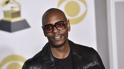 """Dave Chappelle poses in the press room with the best comedy album award for """"The Age of Spin"""" and """"Deep in the Heart of Texas"""" at the 60th annual Grammy Awards in New York on Jan. 28, 2018."""