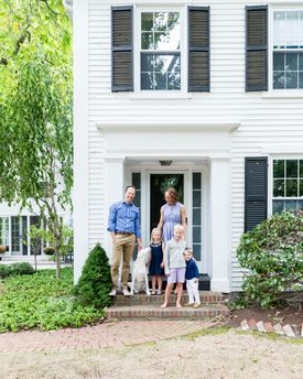 Will and Lindsey Burghardt with children Tess,  Emmett, and Harris in front of  their Greek Revival home in Duxbury.