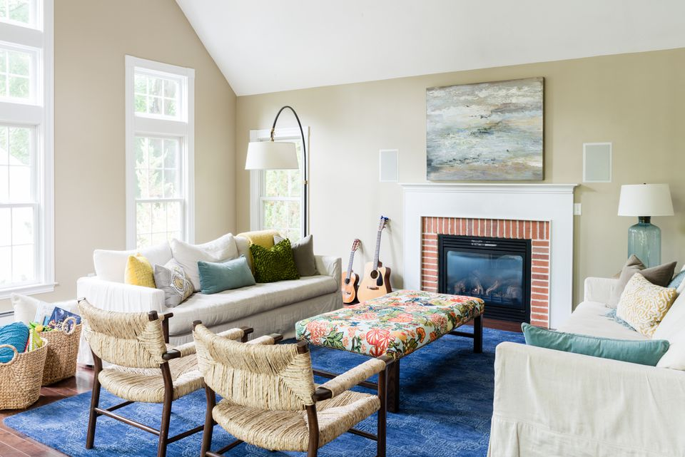 To liven up the neutral  living room, designer Beth Bourque introduced a navy blue rug and a bench upholstered with a vibrant Schumacher fabric. On the linen slipcovered sofas, throw pillows  in a mix of hues draw the eye  and add textural interest.