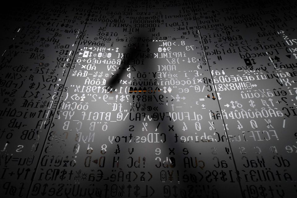 An employee walked behind a glass wall with machine coding symbols at the headquarters of Internet security giant Kaspersky in Moscow.