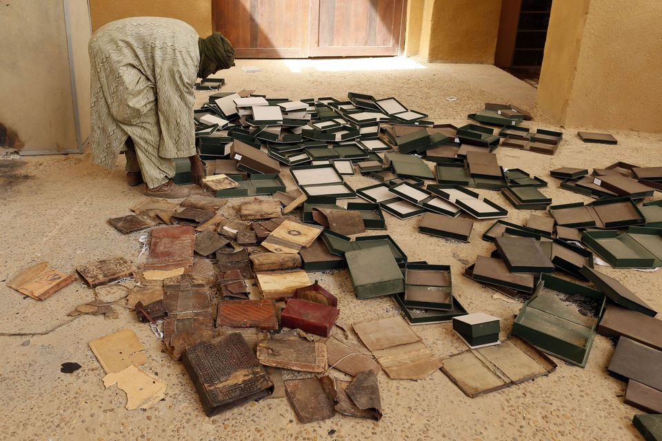 A museum guard worked around boxes that held ancient manuscripts that were partially damaged when rebels set fire to the Ahmed Baba Institute.