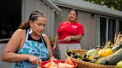 Rachael Devaney speaks with fellow Eastern Woodlands Rematriation Collective member Kristen Wyman while preparing fruits and vegetables in Centerville.