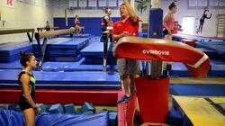 Coach Mihai Brestyan instructed Sophia Voss during her vault exercise at Brestyan's American Gymnastics Club in Burlington.