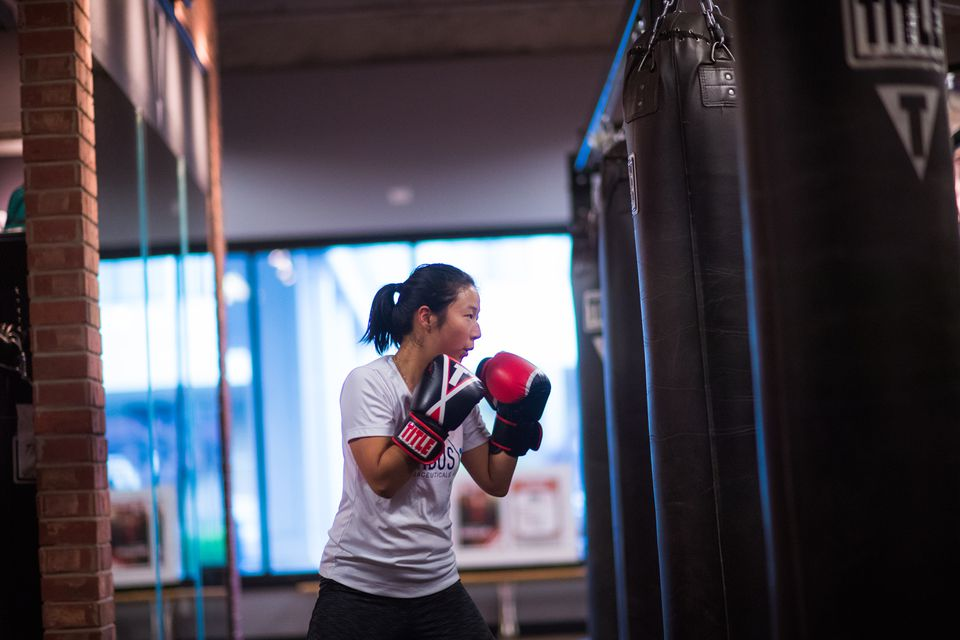 Jungeun Lee, a senior accountant at Corbus Pharmaceuticals practices her form during a boxing class at TITLE Boxing Club in Norwood on Tuesday.