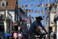 Pedestrians walk along Commerce Street in Provincetown, Mass., as rainbow banners hang over the street between shops and houses.