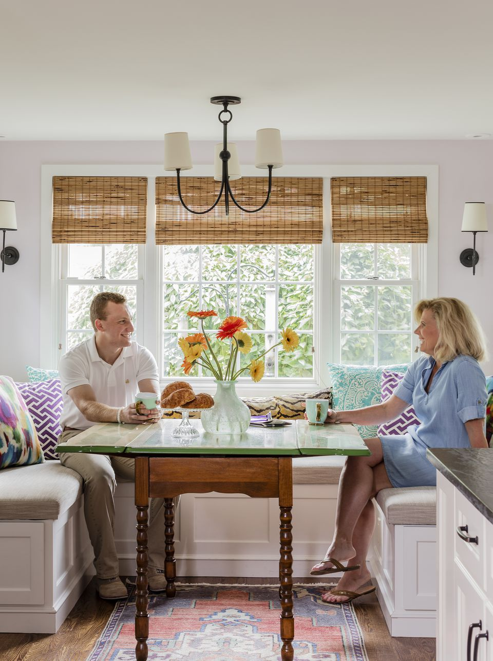 Linda Shpilner and son Zachary sit at the breakfast-area table, inherited from Linda's aunt. Romo fabric covers the three-sided built-in banquette.