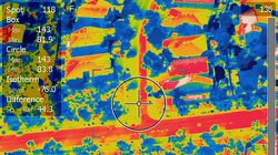 """This Arizona State University thermal image photo shows a Phoenix street coated half with new, lighter-colored pavement to the left of the crosshairs, showing as much cooler in yellow than the original blacktop at right in red, on Sept. 10, 2020. A team from Arizona State University is working with the city of Phoenix on a pilot program studying the use of """"cool pavement"""" to reduce the heat island effect, a phenomenon that raises temperatures in urban areas covered by asphalt and concrete."""
